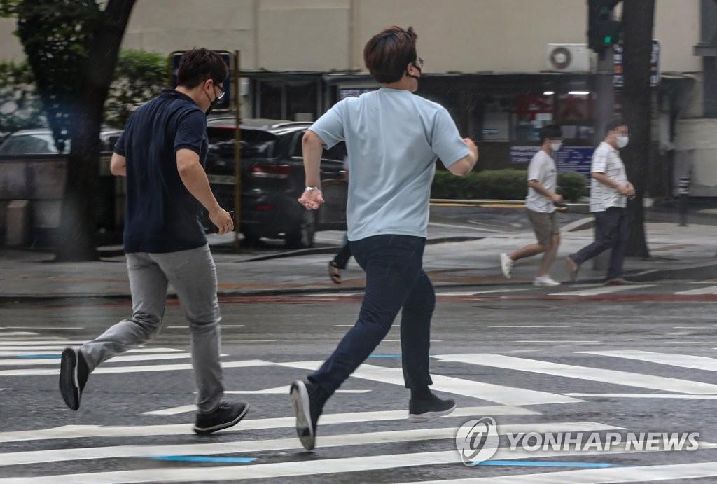 资料图片:7月19日,在首尔光化门,没带雨具的市民快步前往建筑物内躲避阵雨。 韩联社