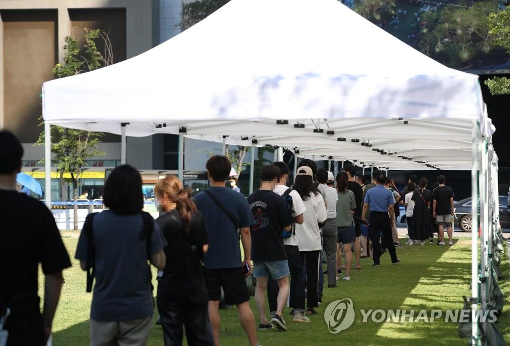 资料图片:市民在临时筛查诊所前排长队等待接受病毒检测。 韩联社