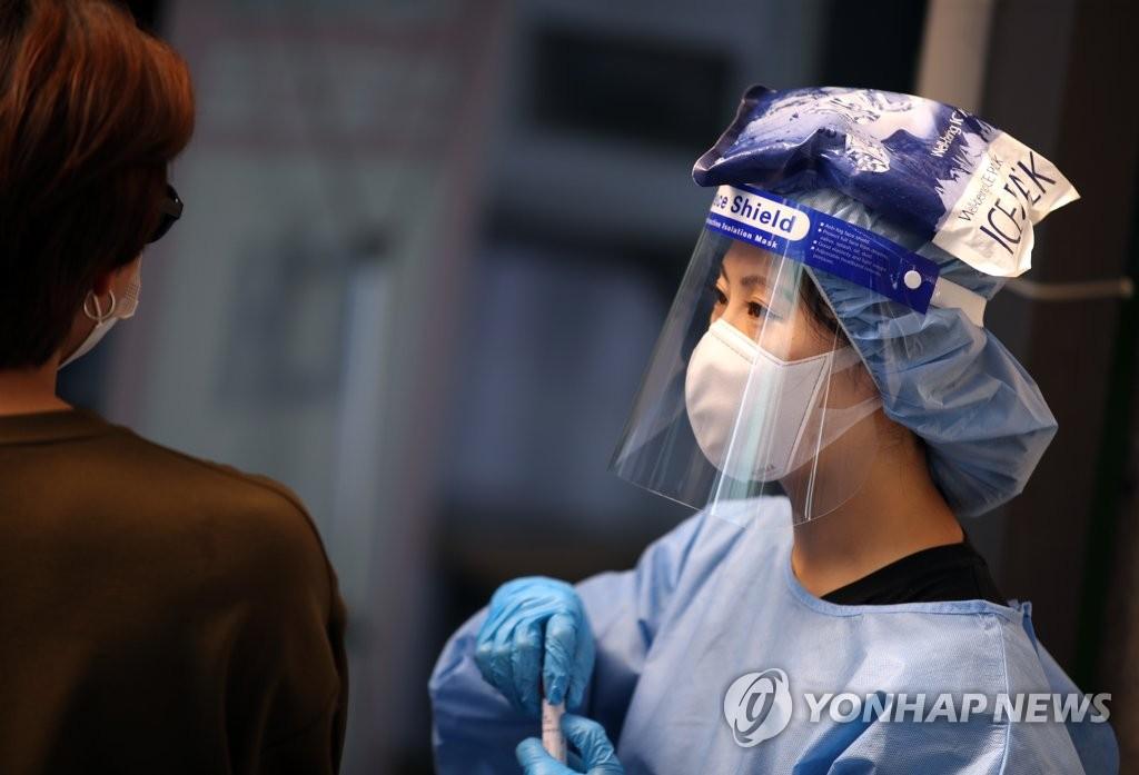资料图片:7月21日,在首尔铜雀区卫生站的筛查诊所,一名医务人员身穿防护服,头顶冰袋消暑。 韩联社