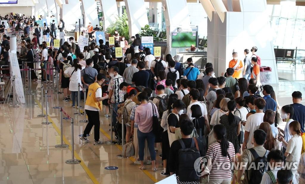 资料图片:7月22日,金浦国际机场国内出发大厅人潮拥挤。 韩联社
