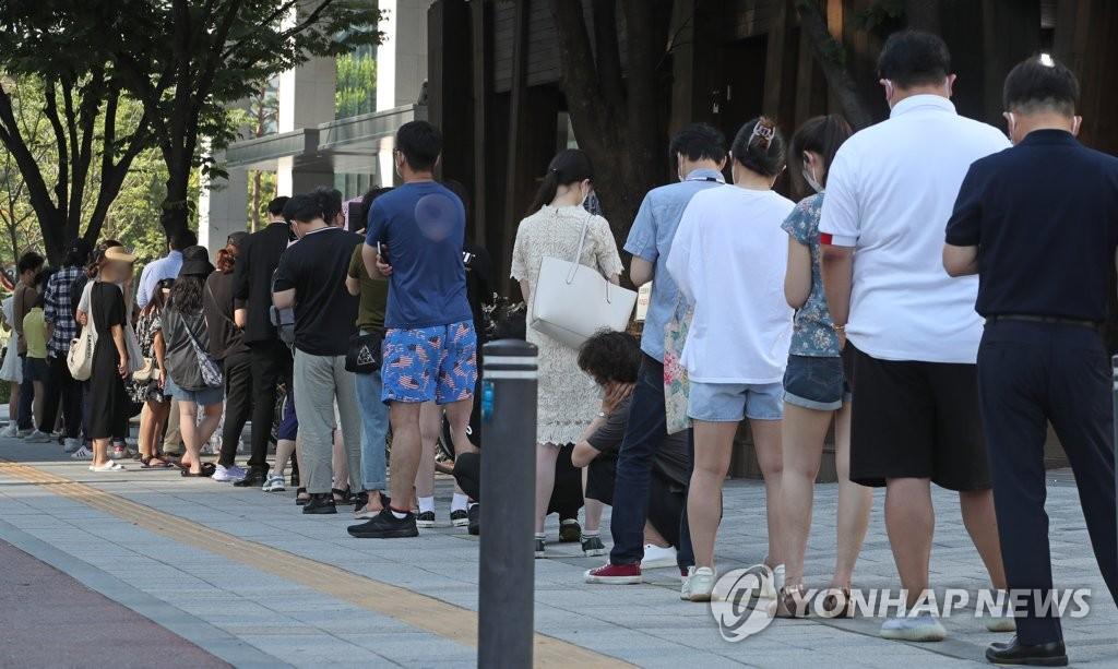 资料图片:7月22日,在首尔松坡区卫生站的筛查诊所,市民排队待检。 韩联社