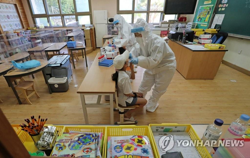 资料图片:医务人员在教室里为学生进行新冠检测采样。 韩联社