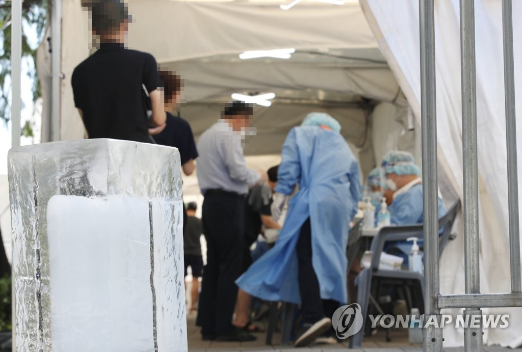 资料图片:7月22日下午,在首尔落星垈公园内的临时筛查诊所,巨大的冰块为医务人员带来些许清凉。 韩联社