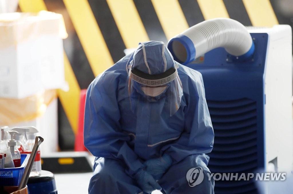 资料图片:7月22日,在光州市北区的筛查诊所,卫生站医务人员正在吹冷风消暑。 韩联社/光州北区政府供图(图片严禁转载复制)