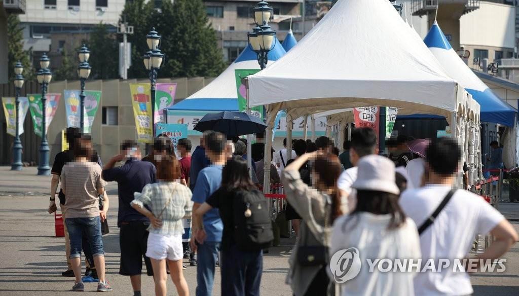 资料图片:市民在烈日下排队候检。 韩联社