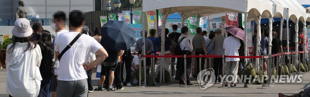7月23日,在设于首尔站广场的临时筛查诊所,市民排队接受病毒检测。 韩联社