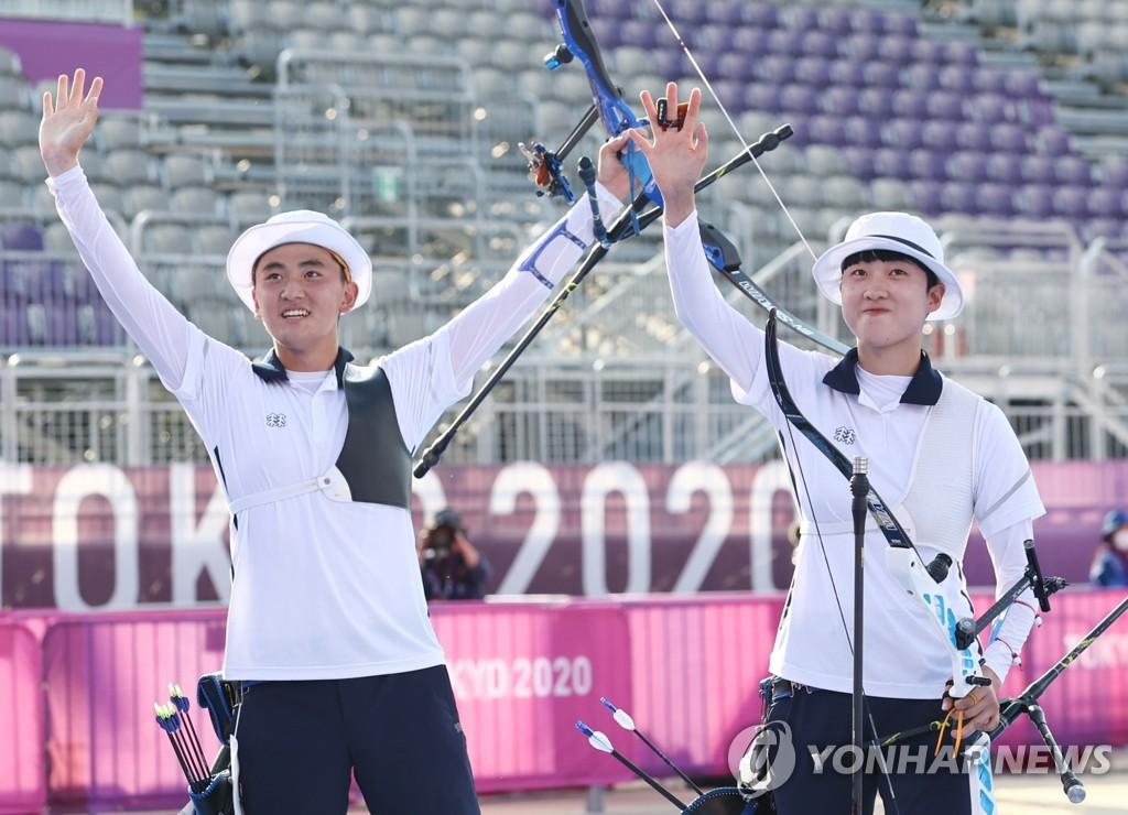 7月24日,在东京梦之岛公园,韩国射箭运动员金济德(左)和安山举起金牌庆祝夺金。在当天下午进行的东京奥运会射箭混合团体决赛上,金济德/安山组合以5比3力压荷兰队,夺得金牌。 韩联社