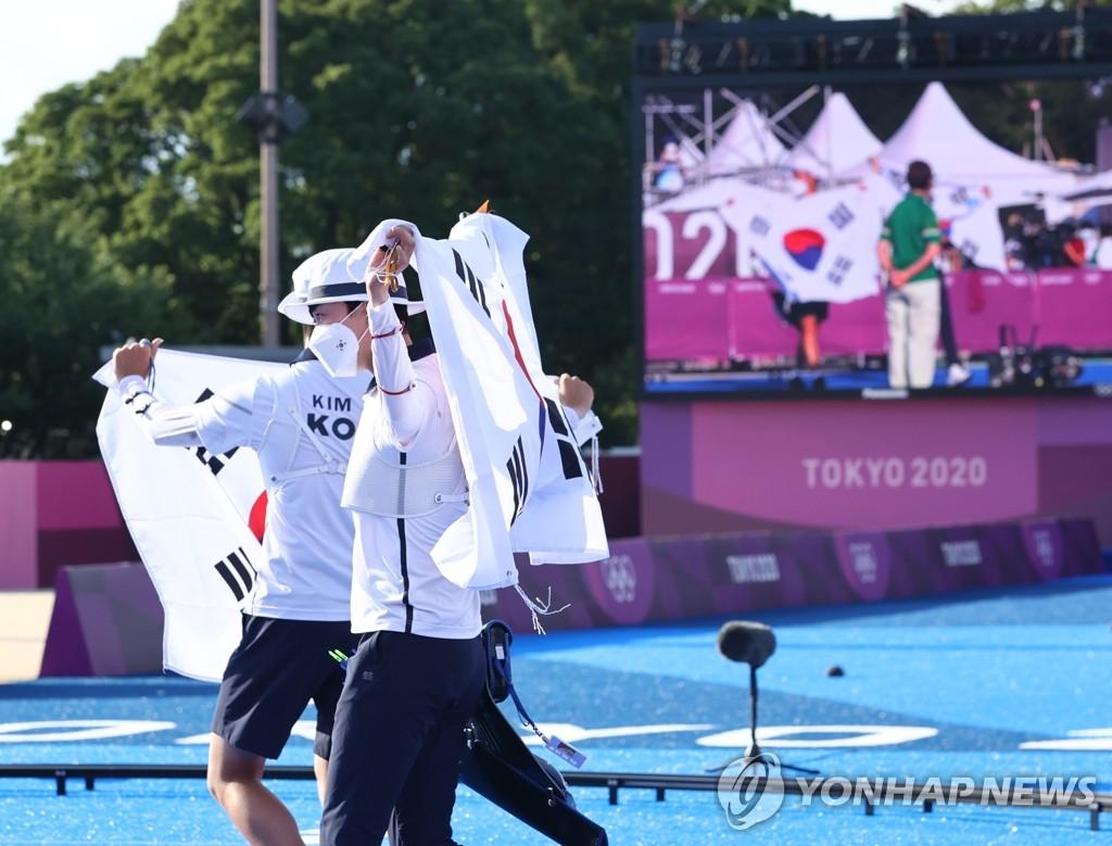 7月24日,在东京梦之岛公园,韩国射箭运动员金济德和安山夺金后举旗庆祝。在当天下午进行的东京奥运会射箭混合团体决赛上,金济德/安山组合以5比3力压荷兰队,夺得金牌。 韩联社