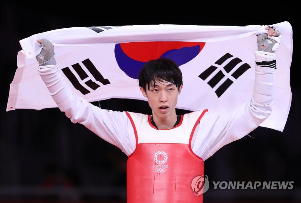 7月24日,在东京幕张展览馆,韩国跆拳道运动员张准夺得男子58公斤级铜牌后高举国旗庆祝。 韩联社
