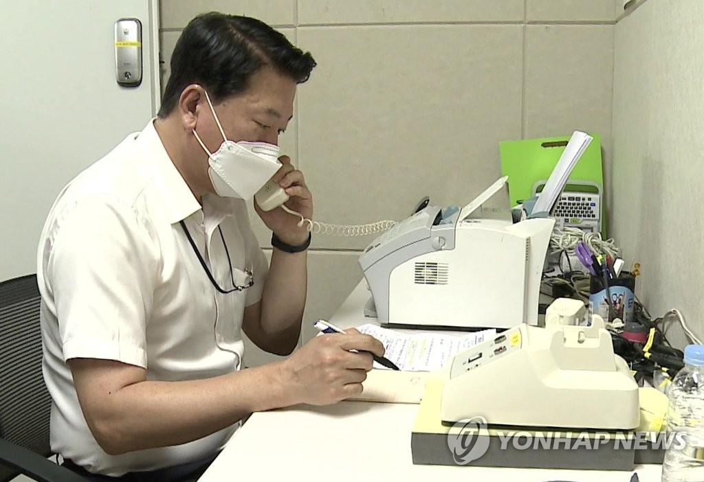 """资料图片:7月27日,在韩朝联络办公室所属首尔分处,韩方联络人员通过""""韩朝直通电话""""与朝方通电话。这是韩朝通信联络渠道时隔413天重启。 韩联社/统一部供图(图片严禁转载复制) 韩联社"""
