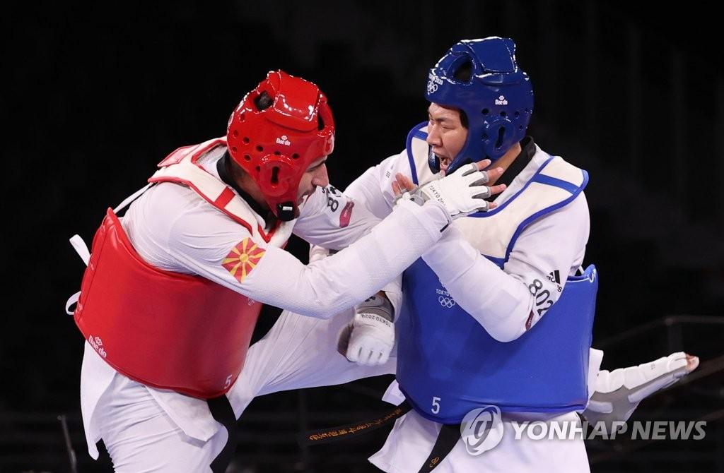 7月27日晚,在日本幕张展览馆A厅举行的东京奥运会跆拳道男子80公斤以上级铜牌战中,韩国选手印教敦(蓝衣)以5比4击败斯洛文尼亚的伊万·特拉伊科维奇,拿下铜牌。 韩联社