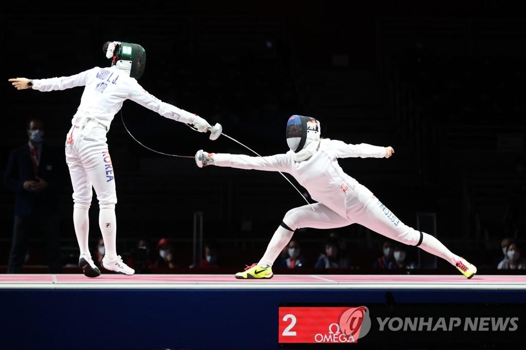 7月27日晚,在东京奥运会女子重剑团体决赛中,韩国队以32比36不敌爱沙尼亚队夺得银牌。图为崔仁贞(左)击中对手得分。 韩联社