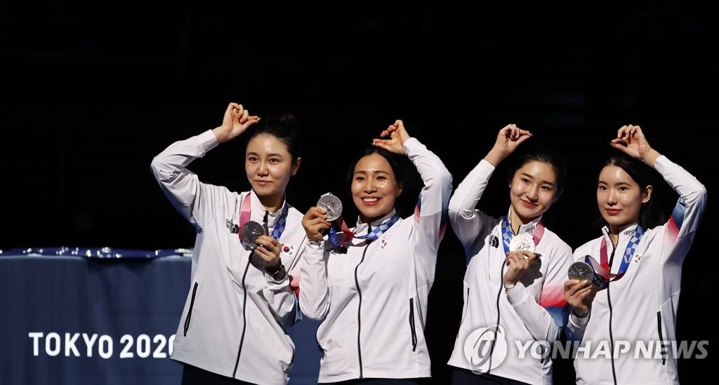 7月27日晚,在日本千叶幕张展览馆举行的东京奥运会女子重剑团体决赛中,韩国队不敌爱沙尼亚队,摘得银牌。图为韩国重剑女团举起银牌合影。 韩联社