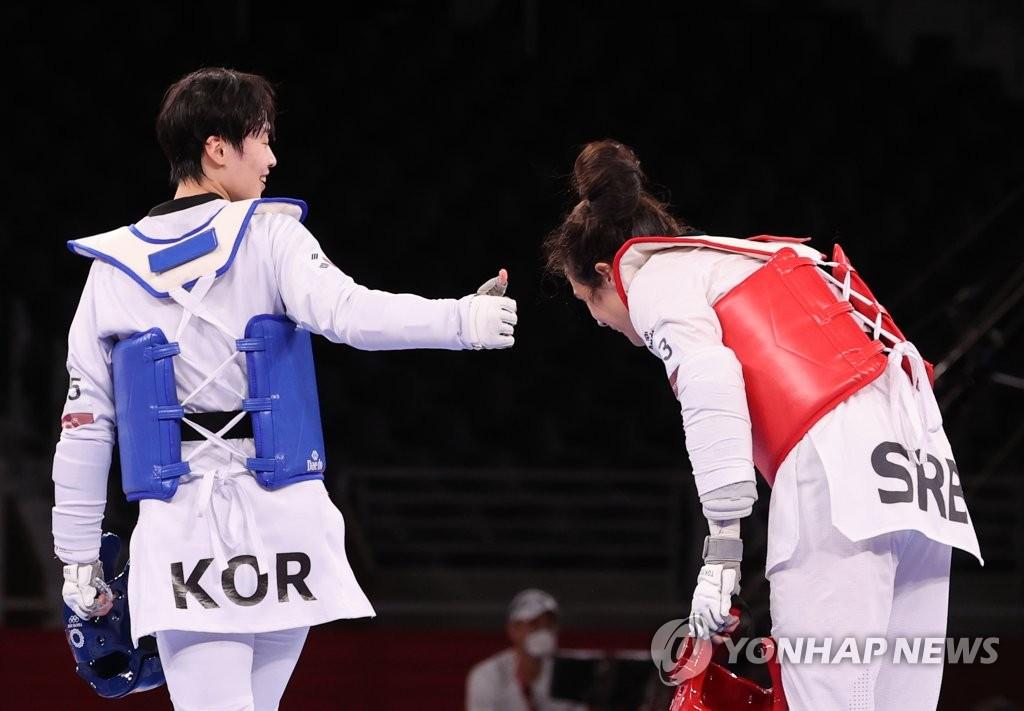 7月27日,东京奥运会女子跆拳道67公斤以上级决赛在幕张国际会展中心A展厅进行。韩国选手李多嫔对阵塞尔维亚老将米莉察·曼迪奇,最终以7比10遗憾败北获得银牌。图为李多嫔向米莉察·曼迪奇举大拇指致敬。 韩联社
