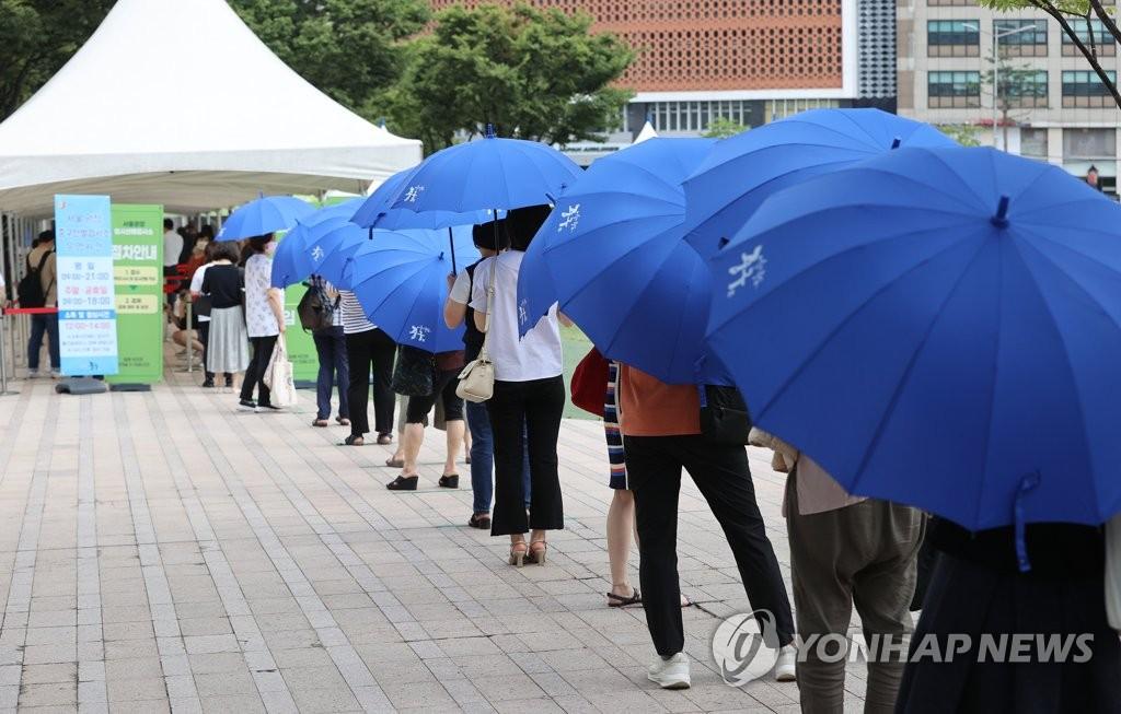 资料图片:7月28日,在首尔广场的临时筛查诊所,市民排长龙待检。 韩联社