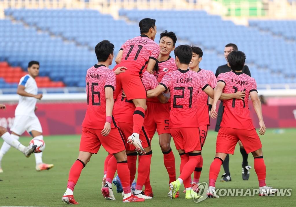 7月28日,东京奥运会男子足球小组赛B组第三轮比赛在横滨国际综合竞技场举行,韩国队迎战洪都拉斯队。图为韩国队元斗载主罚进球后,队员们相拥庆祝。 韩联社