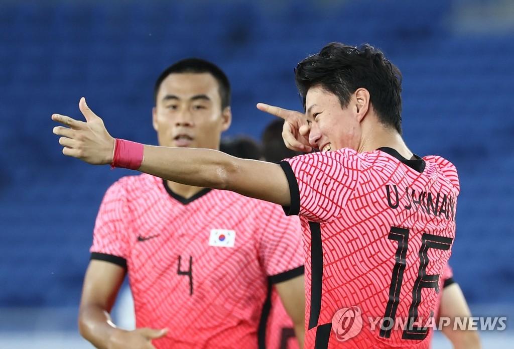 7月28日,在日本横滨国际综合竞技场,韩国队黄义助(右)摆出射箭姿势庆祝进球。 韩联社