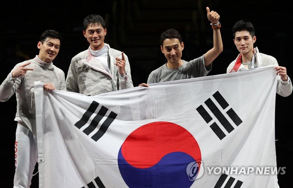 7月28日,东京奥运男子团体佩剑决赛在日本千叶幕张展览馆举行。由吴尚旭、具本佶、金政焕和替补的金准镐组成的韩国击剑队以45比26的比分战胜意大利夺冠。图为韩国队举国旗合影。 韩联社