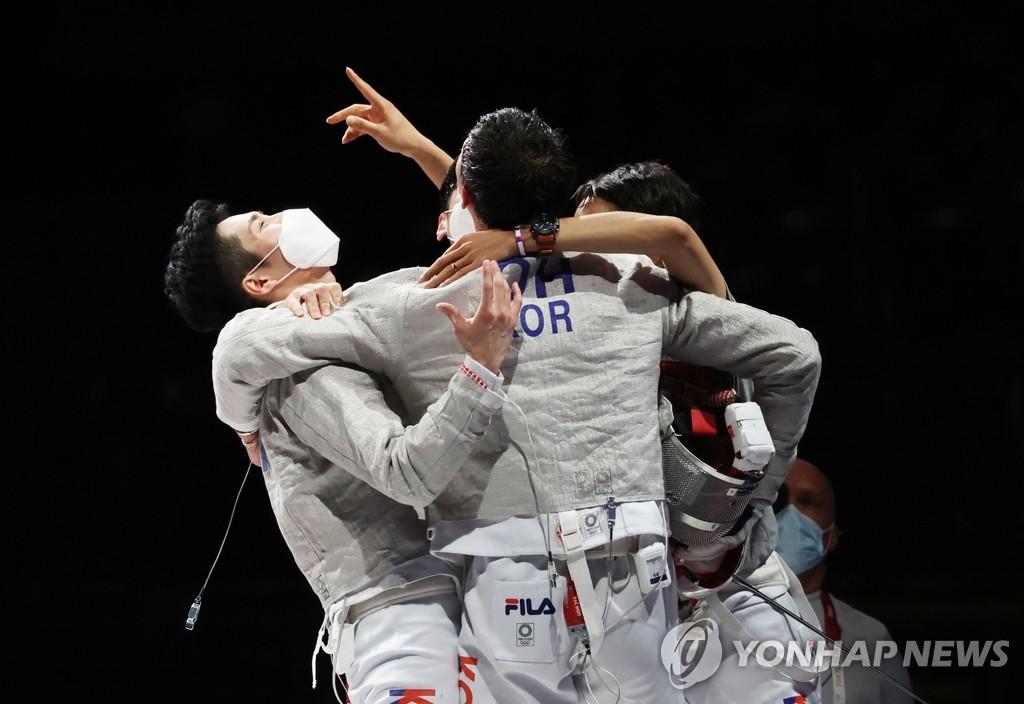 7月28日,东京奥运男子团体佩剑决赛在日本千叶幕张展览馆举行。由吴尚旭、具本佶、金政焕和替补的金准镐组成的韩国击剑队以45比26的比分战胜意大利夺冠。图为韩国队庆祝胜利。 韩联社