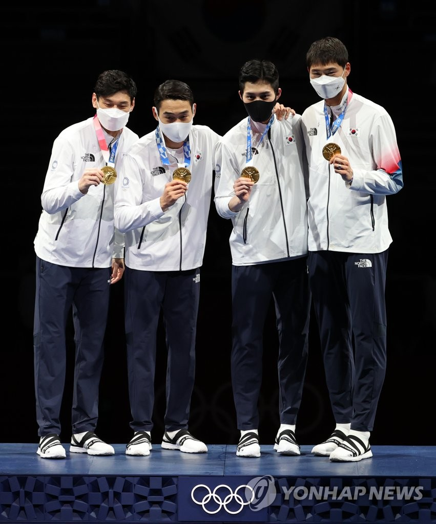 7月28日,东京奥运男子团体佩剑决赛在日本千叶幕张展览馆举行。由吴尚旭、具本佶、金政焕和替补的金准镐组成的韩国击剑队以45比26的比分战胜意大利夺冠。图为韩国队举金牌合影。 韩联社