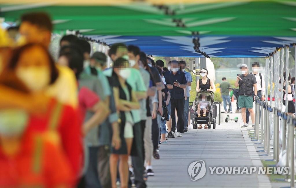 资料图片:7月29日,在首尔江南地区COEX前设置的临时筛查诊所,人们排队等待核酸检测。 韩联社