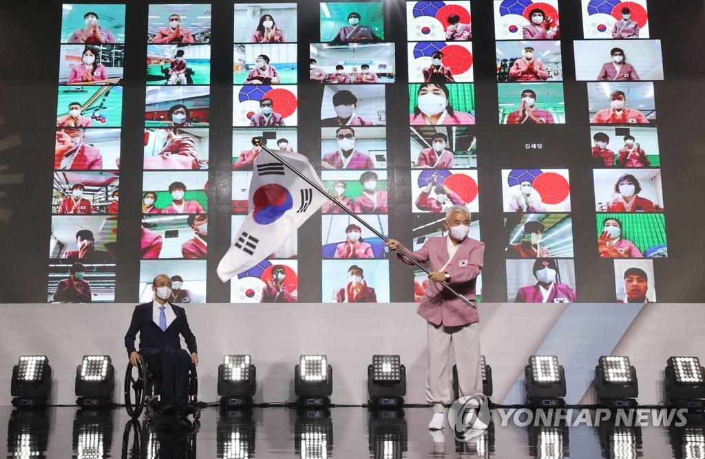 7月29日,在京畿道利川运动员村,2020东京残奥会韩国体育代表团举行成团仪式。图为代表团团长朱元洪挥动太极旗。 韩联社