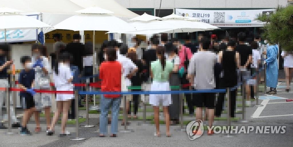 资料图片:在一处临时筛查诊所,市民排队候检。 韩联社