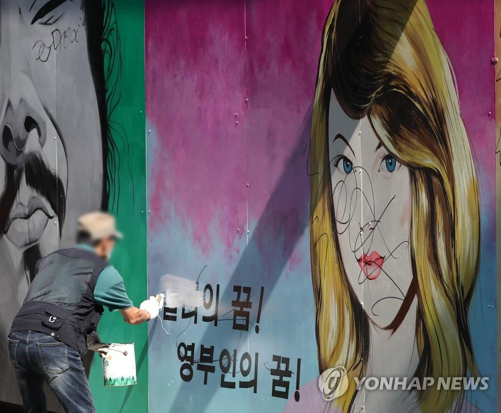 7月30日,首尔一家二手书店员工正在油漆引发争议的壁画字句。 韩联社