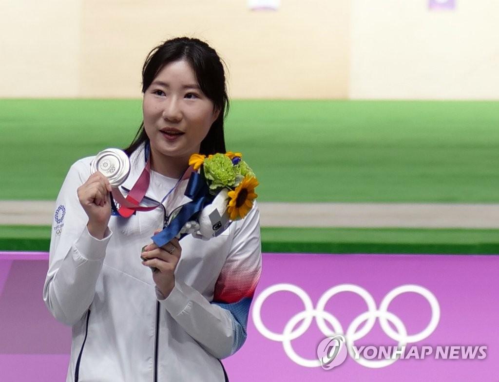 7月30日,在日本东京朝霞射击训练场,韩国射击运动员金珉静在东京奥运女子25米手枪决赛上斩获银牌。图为金珉静在颁奖仪式上展示银牌。 韩联社