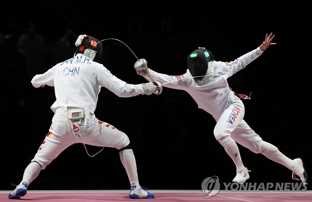 7月30日,在日本幕张展览馆举行的东京奥运会男子重剑团体赛铜牌争夺战赛场,韩国队迎战中国队。图为韩国队朴相永刺中得分。 韩联社