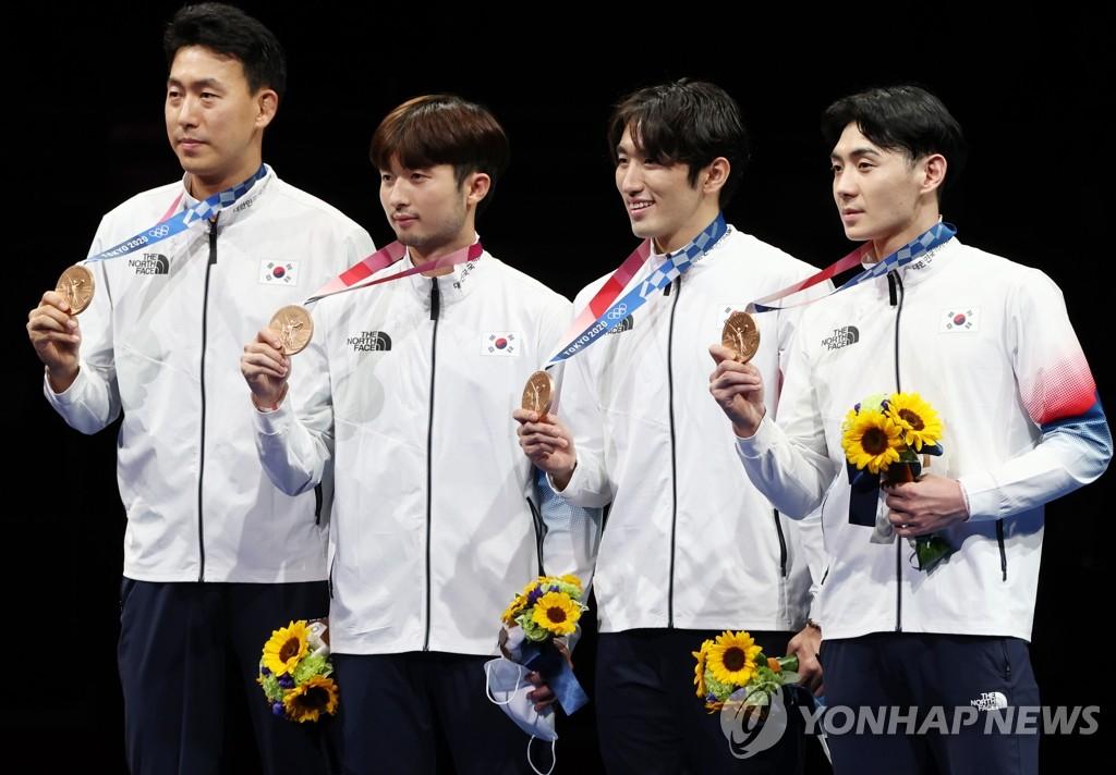 7月30日,在日本幕张展览馆举行的东京奥运会男子团体重剑铜牌赛中,韩国队以45比41战胜中国队,实现男子重剑奖牌零的突破。图为韩国男子重剑队在颁奖仪式上举铜牌合影。 韩联社