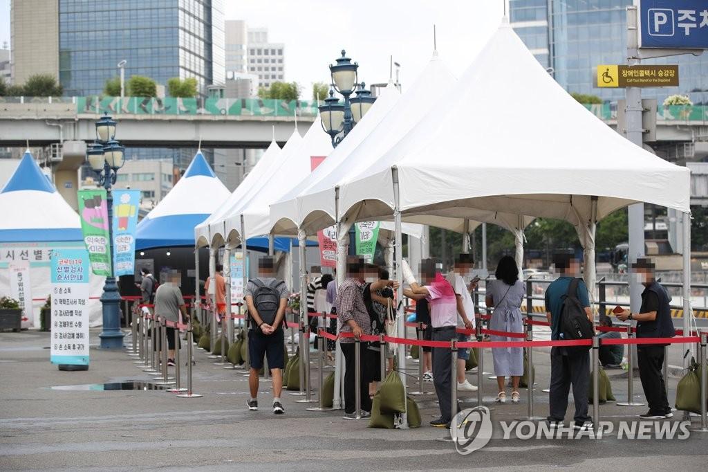 7月31日,在设于首尔站广场的临时筛查诊所,市民排队待检。 韩联社