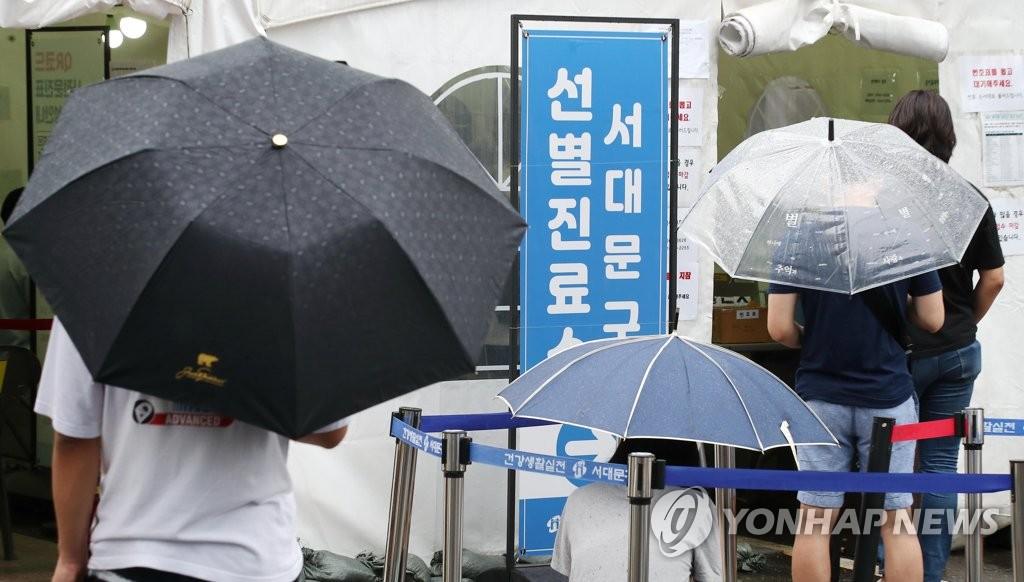 资料图片:8月1日,在首尔西大门区江卫生站前设置的临时筛查诊所,人们撑伞排队等待核酸检测。 韩联社