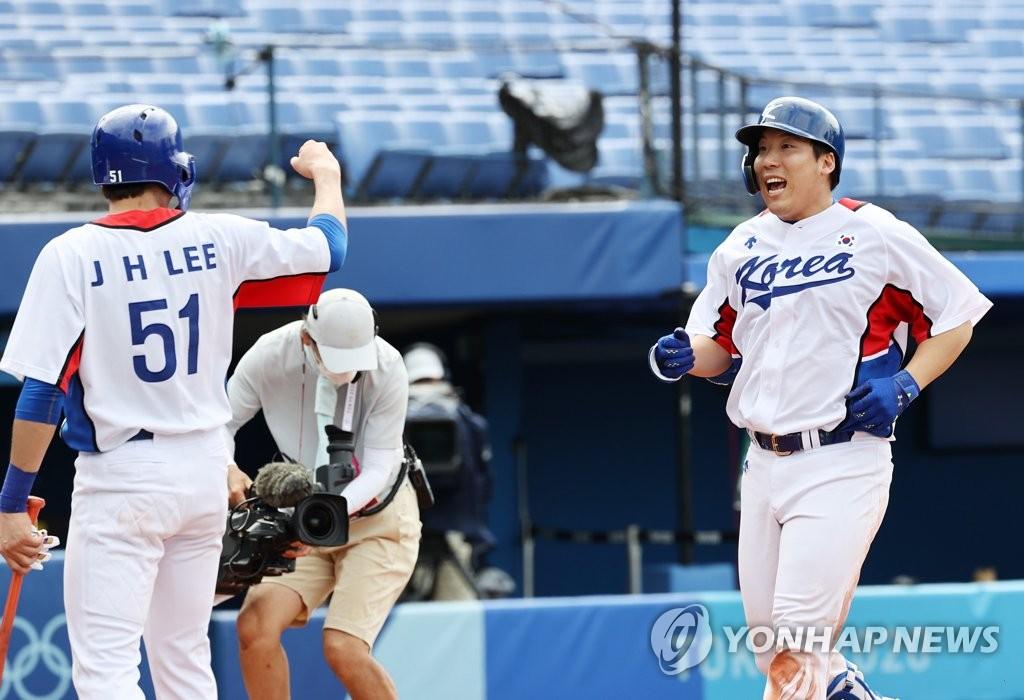 8月2日,东京奥运会棒球淘汰赛第二轮韩国对阵以色列的比赛在日本横滨棒球场进行。图为韩国选手金贤洙(右)打出二分本垒打后庆祝胜利。 韩联社