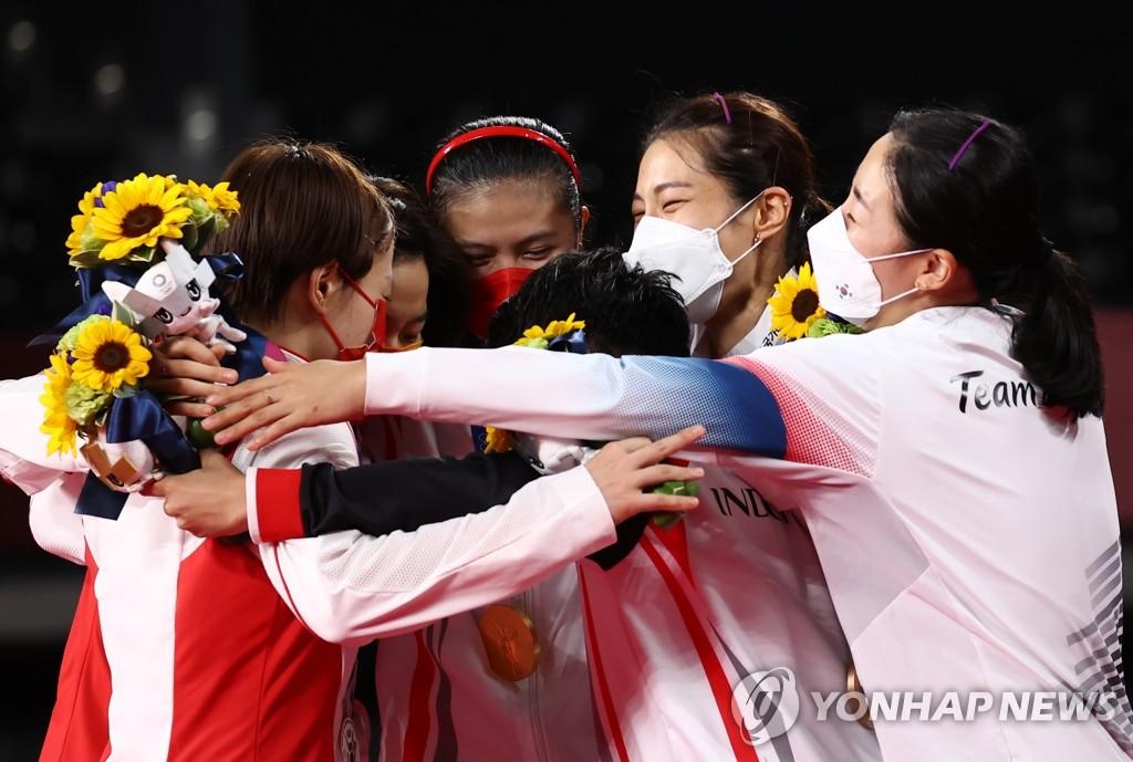 资料图片:8月2日,在日本武藏野之森综合体育广场,东京奥运会羽毛球女子双打赛项目颁奖仪式举行。图为韩国队金昭映(右二)/孔熙容(右一)拿下季军后,与印尼队(冠军)和中国队庆祝。 韩联社