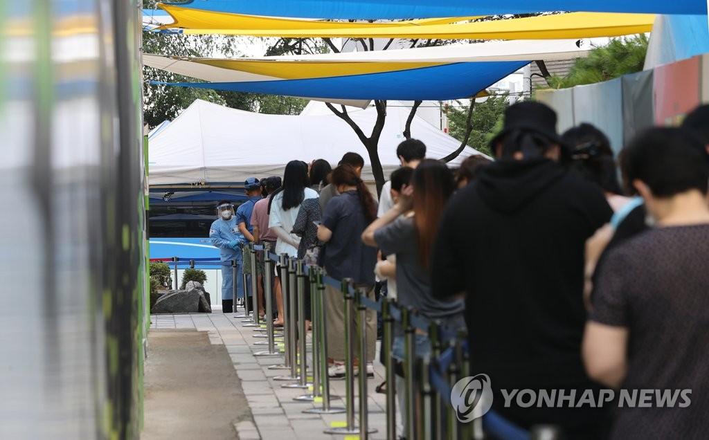 8月4日,在首尔芦原区卫生站筛查诊疗,市民们排长队候检。 韩联社