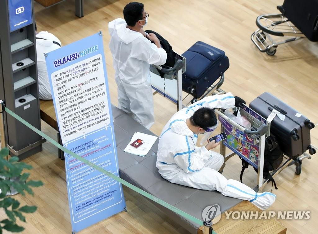 资料图片:8月9日下午,在仁川机场第二航站楼,身穿防护服的入境人员正在等待办理入境手续。 韩联社