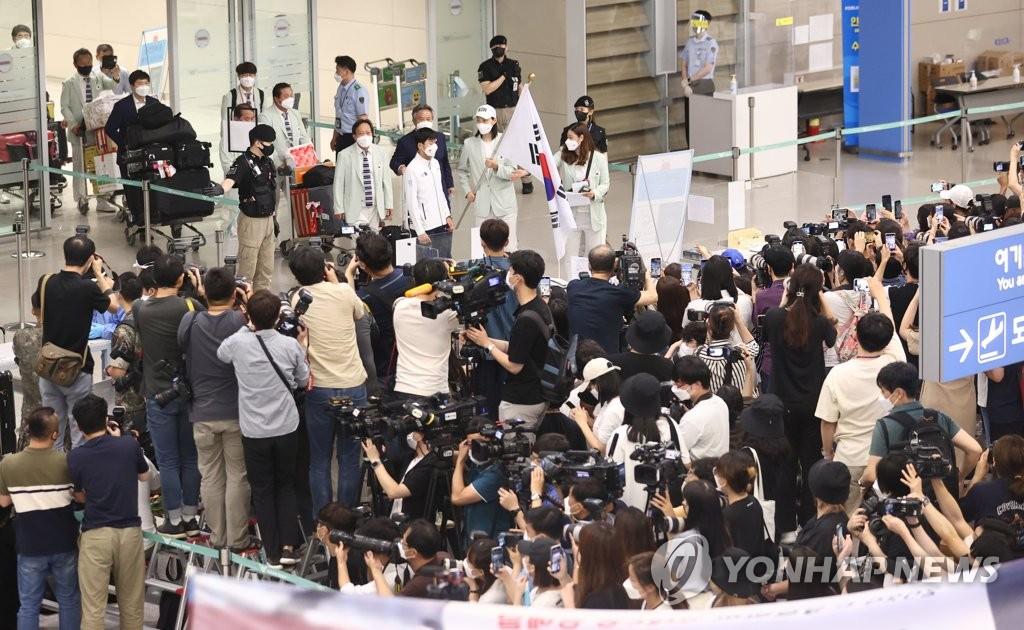 8月9日,在仁川国际机场,载誉回国的韩国女排受到媒体和球迷们的热烈欢迎。 韩联社