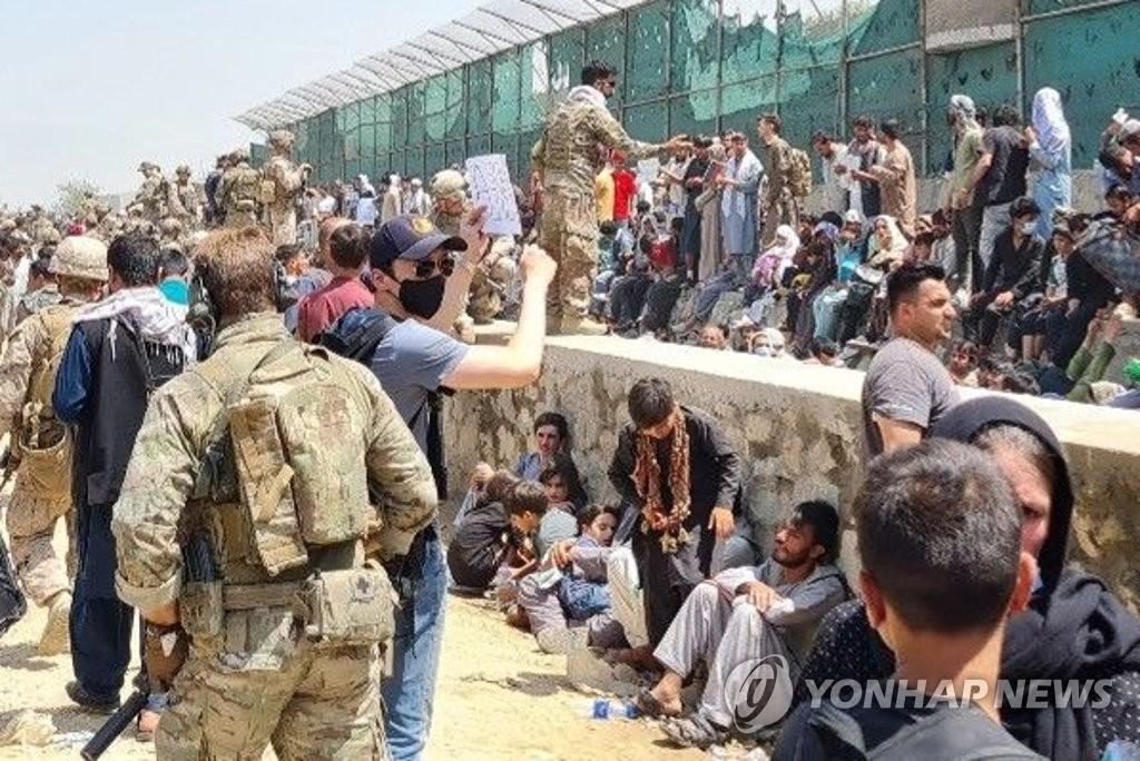资料图片:8月25日,在阿富汗喀布尔机场附近,韩国外交官正在寻找飞赴韩国的阿富汗人。韩军日前派遣3架运输机前往阿富汗及其周边国家帮助曾为韩国工作过的阿富汗人及其家属撤离至韩国。 韩联社/韩国外交部供图(图片严禁转载复制)