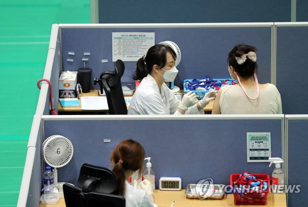 资料图片:在新冠疫苗接种点,医务人员为市民接种疫苗。 韩联社