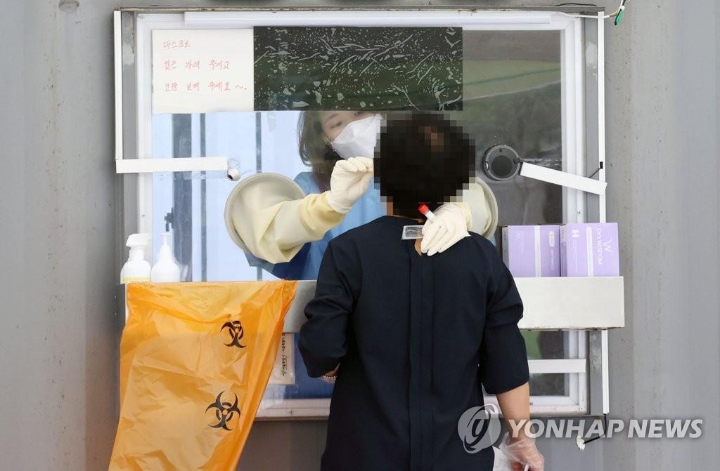 资料图片:医务人员采集病毒样本。 韩联社