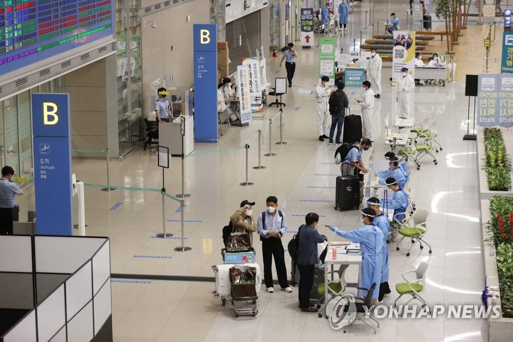 资料图片:8月31日,在仁川国际机场,外国人走入境检疫程序。 韩联社