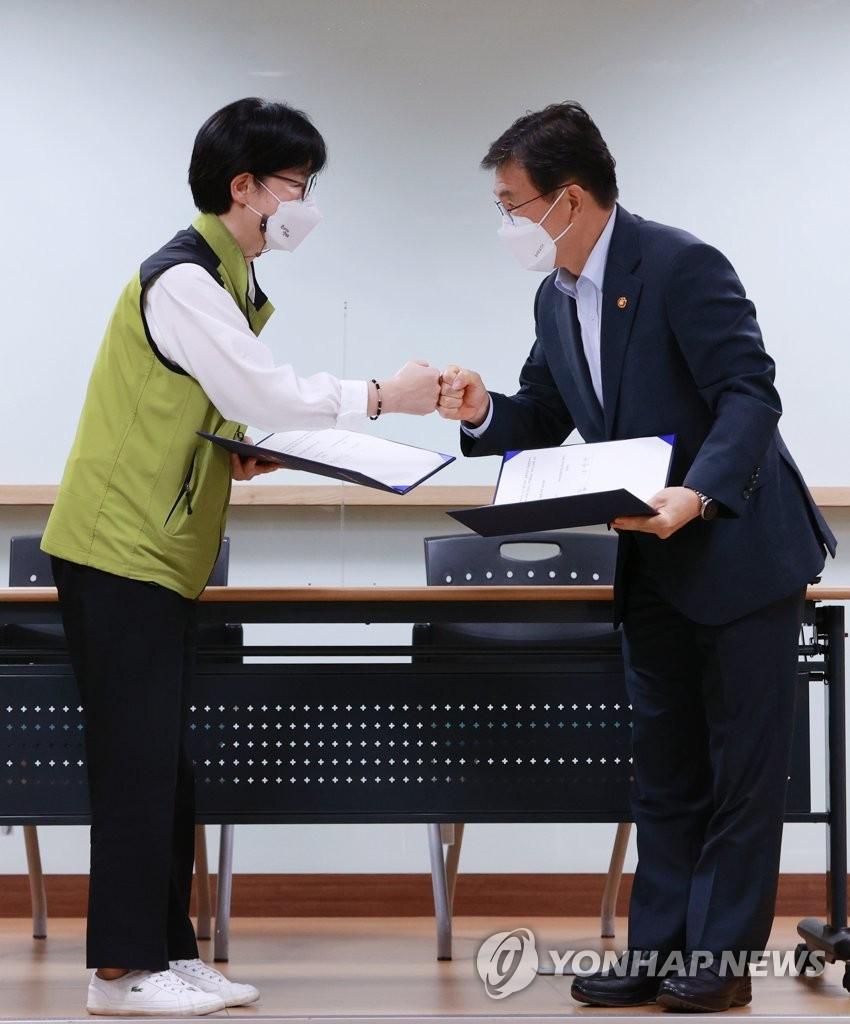 9月2日,在首尔市永登浦区医疗机构评估认证院,保健福祉部长官权德喆(右)与全国保健医疗产业工会主席罗顺子(音)在签署协议前碰拳致意。 韩联社