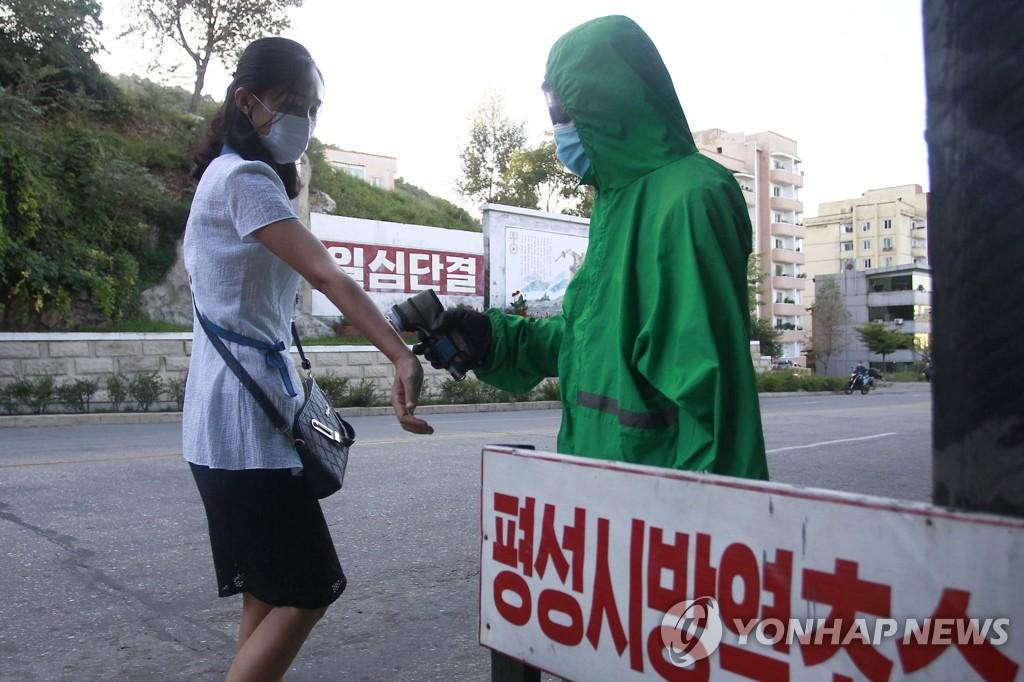 资料图片:9月1日,在朝鲜平安南道平城市,医务人员为居民测温。 韩联社