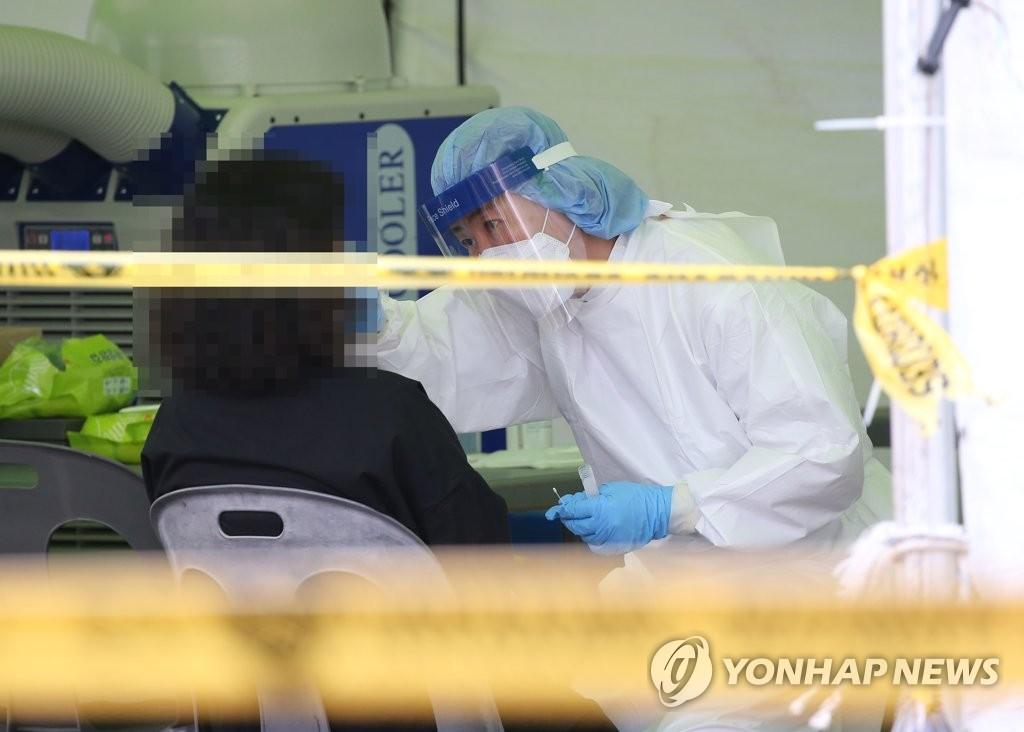 资料图片:9月10日,在设于蔚山市中区综合体育场的核酸检测点,市民接受新冠病毒检测。 韩联社