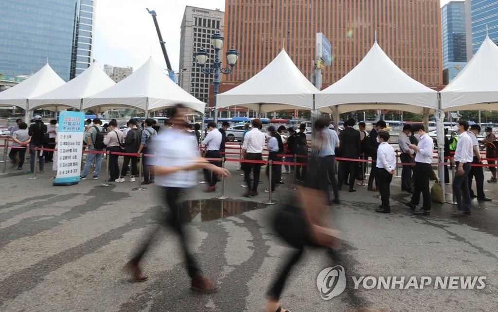 资料图片:9月13日,在首尔火车站广场的临时筛查诊所前,人们排队等待检测新冠病毒。 韩联社