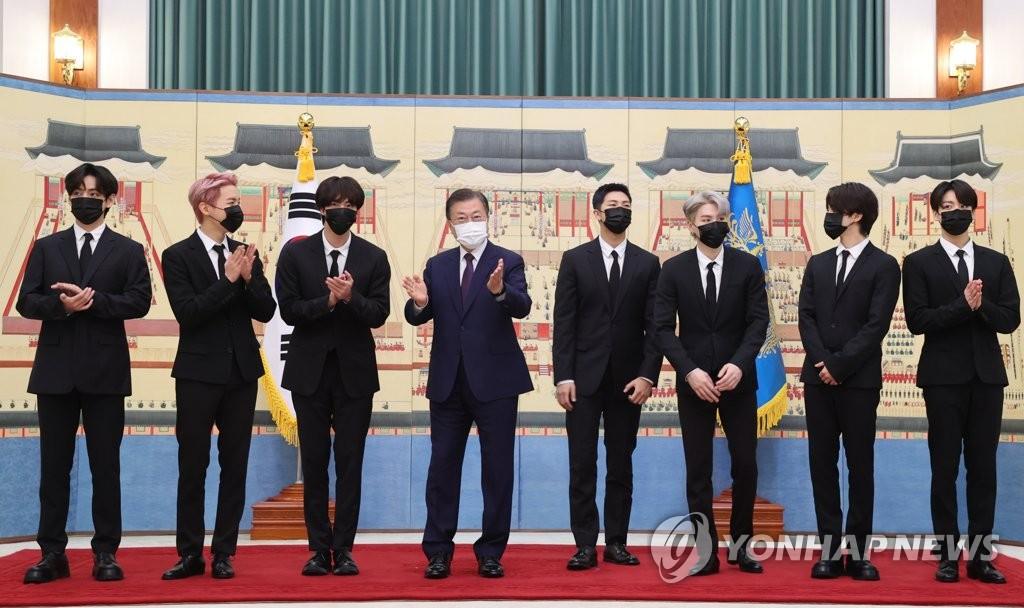"""资料图片:9月14日,在青瓦台,韩国总统文在寅(左四)向防弹少年团(BTS)颁发""""未来一代与文化总统特别使节""""任命书。图为文在寅与防弹少年团合影。 韩联社"""