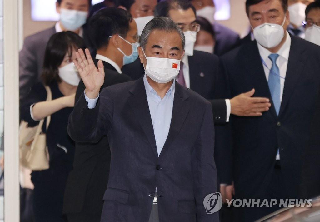 9月14日,中国国务委员兼外长王毅抵达韩国后向媒体记者挥手致意。 韩联社