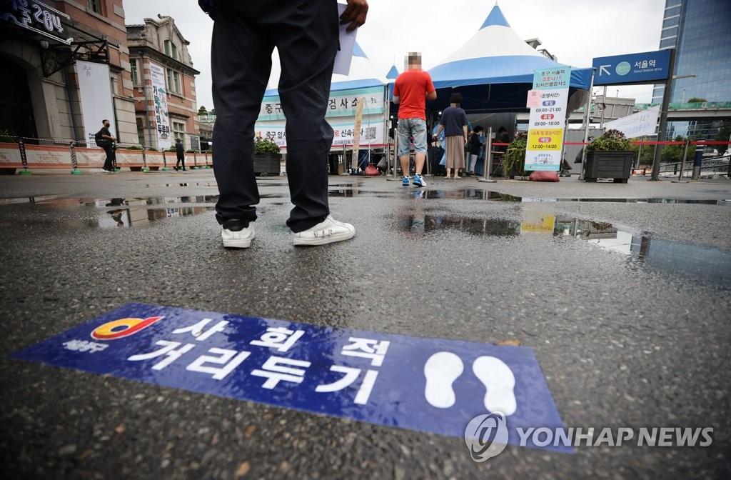 资料图片:9月21日,在首尔广场的临时筛查诊所,人们排队等待病毒检测。 韩联社