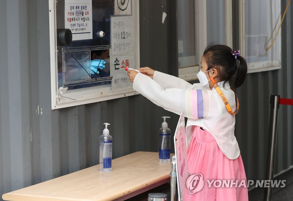 资料图片:9月21日,在首尔火车站的临时筛查诊所,一名小朋友身穿韩服接受新冠病毒检测。 韩联社